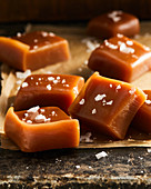 Six salted caramel squares on parchment with salt on top