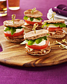 Four sliders on a wood board with meat, tomato, cheese and greens