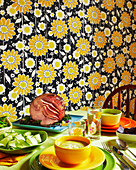 Scene of a fun festive ham dinner with bright wallpaper and colourful dishes