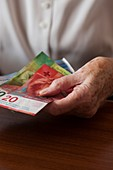 Elderly woman holding Swiss banknotes