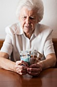 Worried elderly woman counting British banknotes
