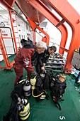 Divers preparing equipment on board ship, Greenland