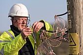 Telephone engineer repairing telephone lines