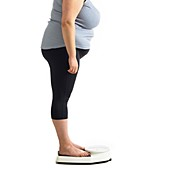 Overweight woman standing on weighing scales
