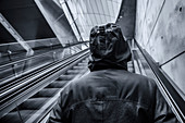 Hooded person on escalator