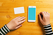 Hands with mobile phone and card