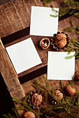 Walnuts, twigs and white paper on wooden surface