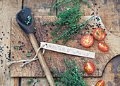 Thyme and tomatoes with a wooden spoon on a wooden board