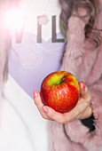 Red and green apple being held in a female hand
