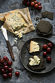 Blue cheese with charcoal biscuits and red grapes