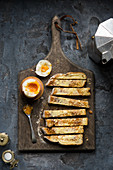 Soft boiled dippy egg with toasted soldiers on a wooden board and moody trendy setting