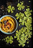 Bowl of morrocan spiced hummus dip with spinach tortilla crisp chips