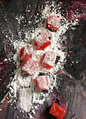 Homemade turkish delight being rolled through icing sugar coating
