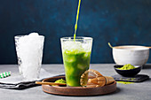 Matcha, green tea ice tea pouring in tall glass on wooden plate