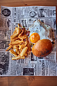 A hamburger with a fried egg and french fries on newspaper