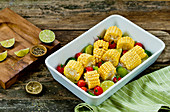 Roasted corn on the cob with cherry tomatoes and limes