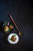 Hasselback potatoes with yoghurt and fresh dill on dark background, flat lay