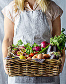 Frau hält Korb mit frischen Lebensmitteln