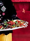 Frau serviert Ratatouille im asiatischen Stil