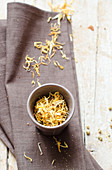 Edible yellow flowers in a bowl and a linen cloth