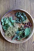 Getrocknete Blätter und Beeren für selbstgemachten Tee in einer Schale