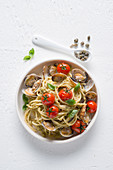 Spaghetti with clams, almond and pistachio pesto, cherry tomatoes and capers