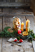 Jar of biscuits and arrangement of candles on rustic wooden surface
