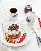 Buckwheat pancakes with fresh berries, honey, sour cream and cup of coffee