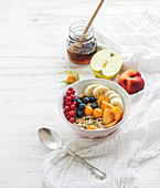 Bowl of oat granola with yogurt, fresh berries, fruit and honey