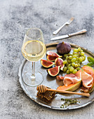 Glass of white wine, honeycomb with drizzlier, figs, melon with prosciutto and grapes