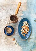 Türkischer Kaffee serviert mit Mandeln und Pistazien