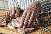 Mann schneidet Pastete in Scheiben