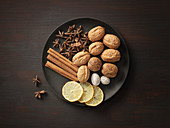 Walnüsse, Zimt, Sternanis, Muskat und Zitronenscheiben auf Teller