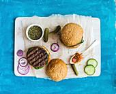 Selbstgemachte Hamburger mit Gurken, Zwiebeln und Sauce