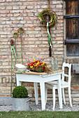 Rot-gelbes Tischgesteck mit Tulpen, Narzissen und Ranunkeln, Kränze aus Zweigen an der Wand