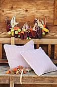 Girlande und kleiner Strauß aus buntem Mais, Kastanien und Lampionfrüchten