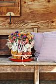 Herbststrauß mit Chrysanthemen und Sommeraster, verkleidet mit buntem Mais