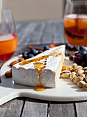 Cheeseboard with brie drizzled with honey, blueberries, almonds and pistachios