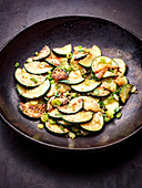 Fried courgette slices with spring onions in a wok (Asia)