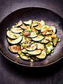 Gebratene Zucchinischeiben mit Frühlingszwiebeln im Wok (Asien)