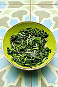 Fried spinach in a green bowl