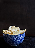 A blue and white bowl with chips, sitting on a dark countertop