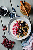 A yogurt bowl with wholegrain oatmeal, berries and grapes