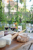 A table laid with cheese, bread and wine in a garden