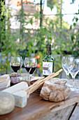 Gedeckter Tisch mit Käse, Brot und Wein im Garten
