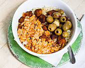 A bowl with rice, tofu, olives and a spicy nut mixture (vegan)
