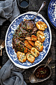Balsamic beef brisket with carrots and potatoes served on a blue patterned plate overhead