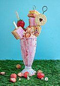 Strawberry freakshake topped with cake, cookies, strawberries and whipped cream