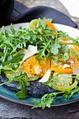 Black pizza with activated charcoal, green and yellow tomatoes, Parmesan cheese and rocket