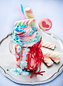 A Freak Shake topped with cream, sprinkles, marshmallows, lollies and strawberry laces